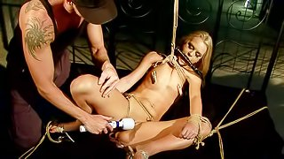 Tied up and lusty blonde slut with nice pale body and shaved beaver, wearing only heels gets stimulated with various sex toys on the sofa in the basement by her master