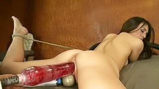 Hot bodied brunette Tiffany Doll with tied legs gets her pussy stretched to the limit by fucking machine with massive fast moving dildo. She gets her pussy ruthlessly drilled with her face down