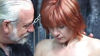 Mature redheaded slave with saggy tits is whipped in hippy's basement